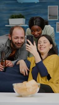 Amis de race mixte se détendre dans le salon pendant la soirée en regardant un film en ligne