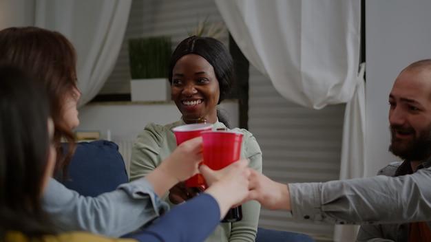 Amis de race mixte socialisant tout en partageant des conseils sur les médias sociaux en se relaxant sur un canapé