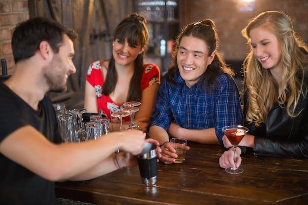 Amis à la recherche de barman faisant des boissons dans un pub