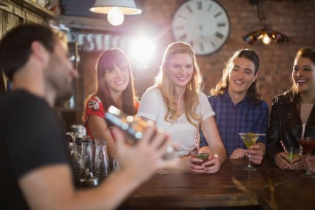 Amis à la recherche de barman faisant des boissons