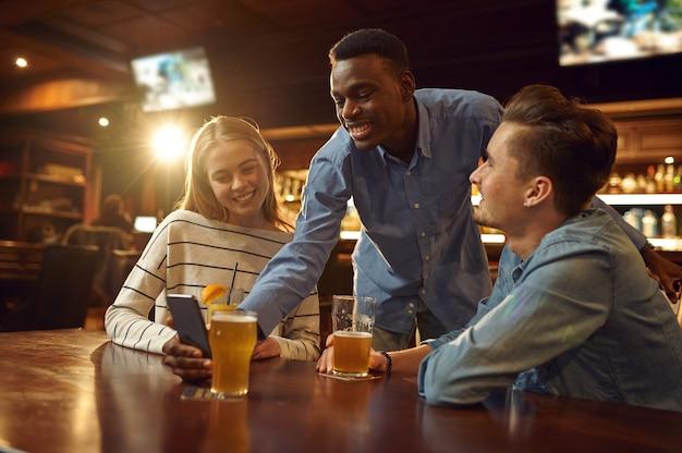 Des amis regardent des photos au téléphone et s'amusent à la table du bar. groupe de personnes se détendre dans un pub, mode de vie nocturne, amitié, célébration de l'événement