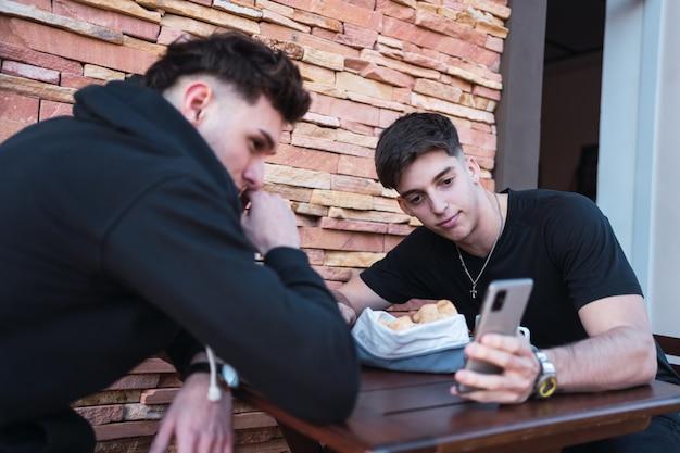 Les amis regardent le smartphone dans le bar extérieur.