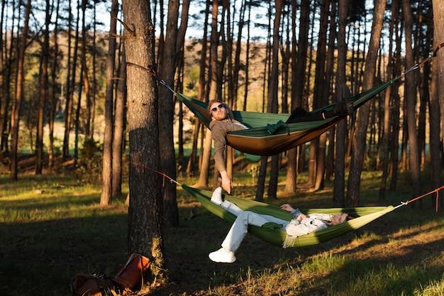 Amis relaxants dans des hamacs en plein plan