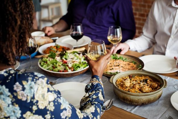 Amis réunis ayant la nourriture italienne ensemble