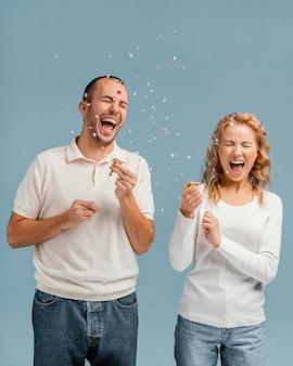 Amis riant et faisant éclater des confettis