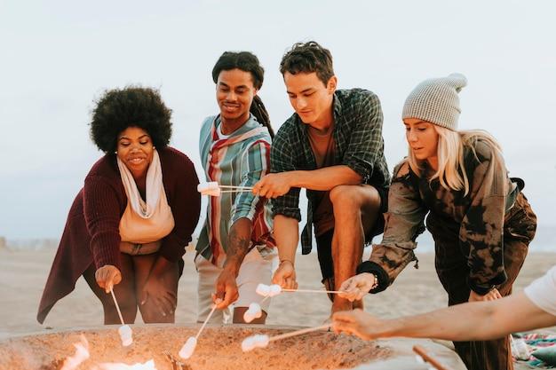 Amis rôtissant des guimauves à la plage