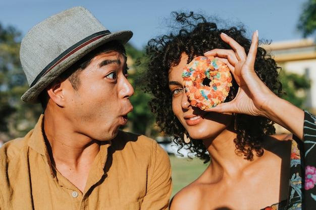 Amis s'amusant avec un beignet