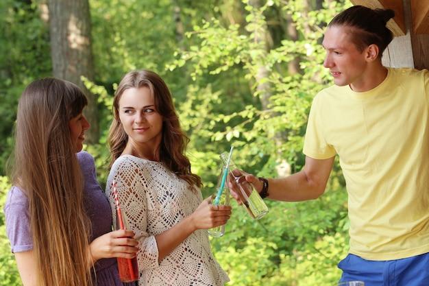 Des amis s'amusant et buvant dans le camp