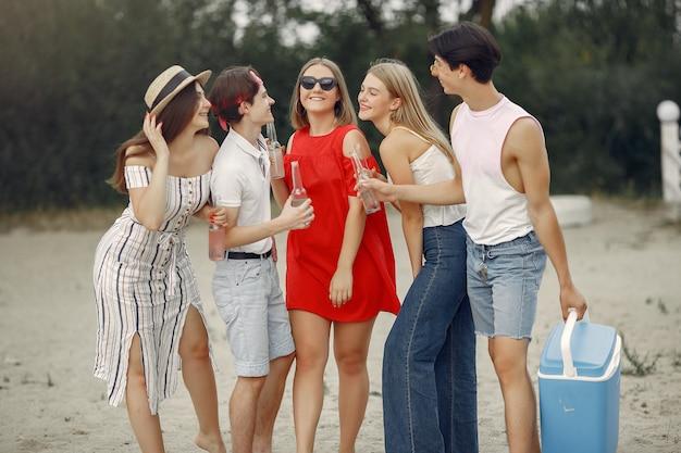 Les amis s'amusent sur une plage avec des boissons