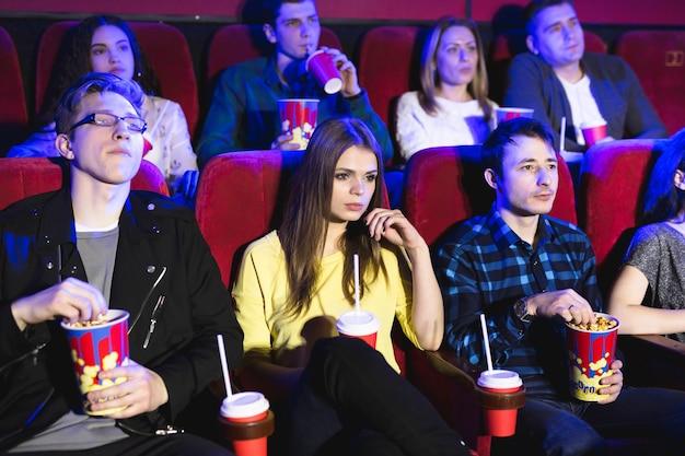 Des amis s'assoient et mangent du pop-corn ensemble tout en regardant des films dans une salle de cinéma