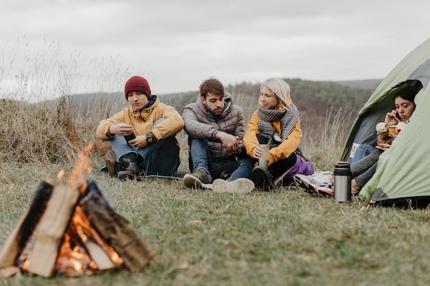 Des amis s'échauffent sur un feu de camp