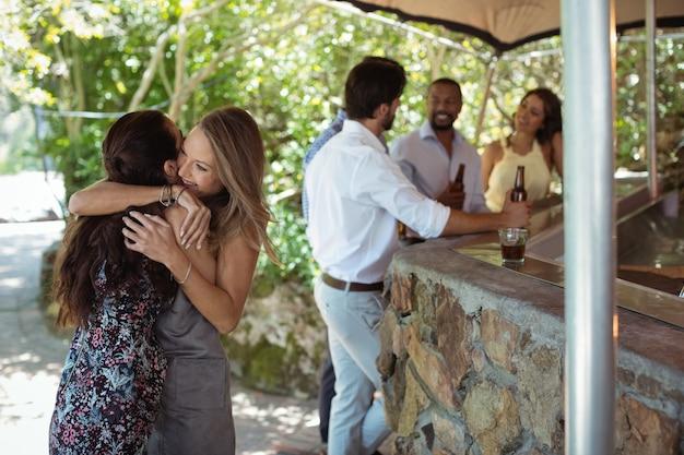 Des amis s'embrassant au comptoir