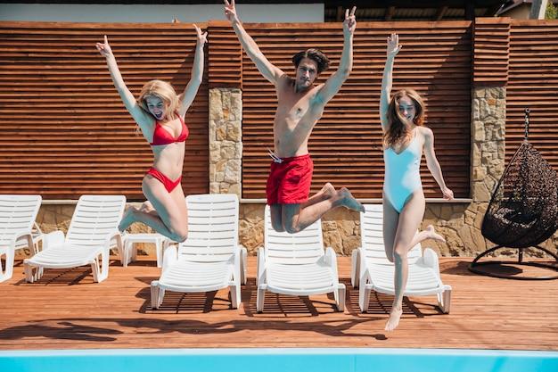 Amis sautant dans la piscine