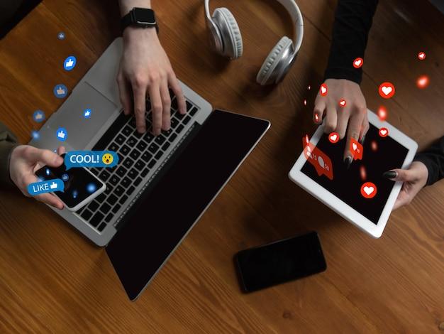 Amis se connectant et partageant avec les médias sociaux, en utilisant un gadget. obtenez des commentaires, des likes, des émotions. icônes d'interface utilisateur modernes, communication, appareils. concept de technologies modernes, de mise en réseau, de gadgets. vue de dessus.