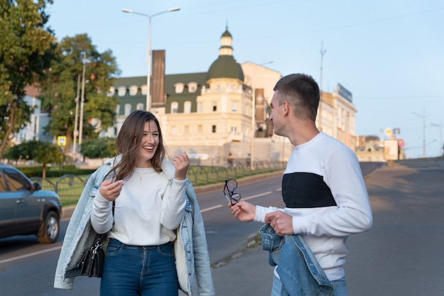 Des amis se promènent en ville et s'amusent. guy et fille discutant avec animation dans la rue.