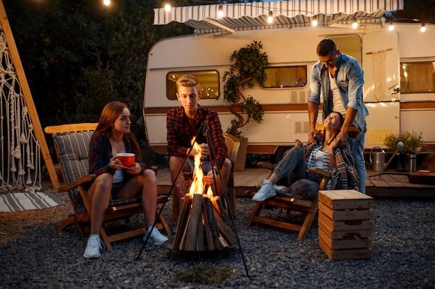 Amis se réchauffant au coin du feu, pique-nique au camping dans la forêt