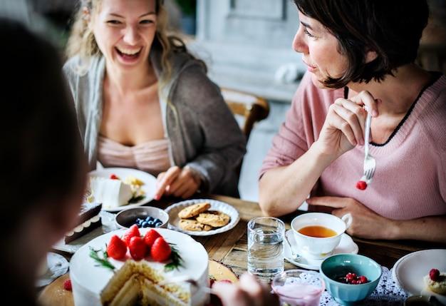 Amis se réunissant pour le thé manger des gâteaux plaisir de bonheur