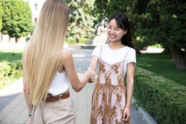 Amis se serrant la main à l'extérieur