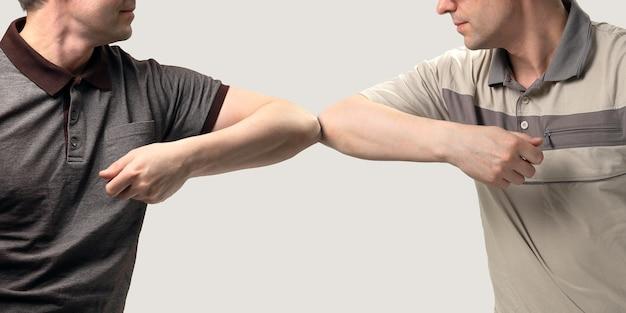 Des amis se sont rencontrés et se sont salués en se cognant les coudes au lieu de se serrer la main