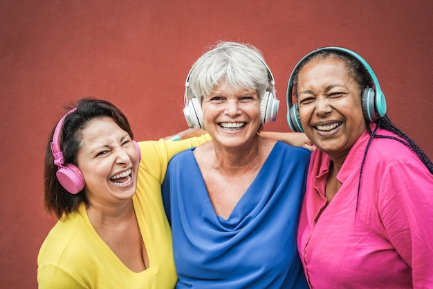 Amis seniors multiraciaux s'amusant à écouter de la musique avec des écouteurs - focus sur le visage de la femme du milieu