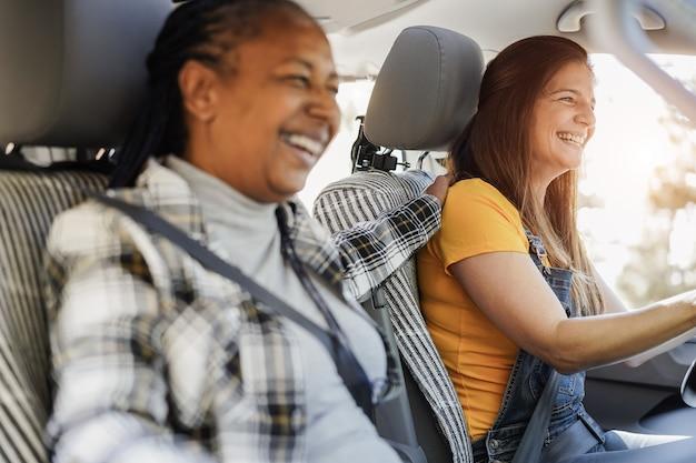 Amis seniors multiraciaux s'amusant sur la route avec un mini camping-car - focus sur le visage de la femme droite