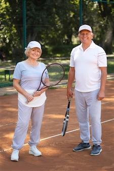Amis seniors en plein coup tenant des raquettes