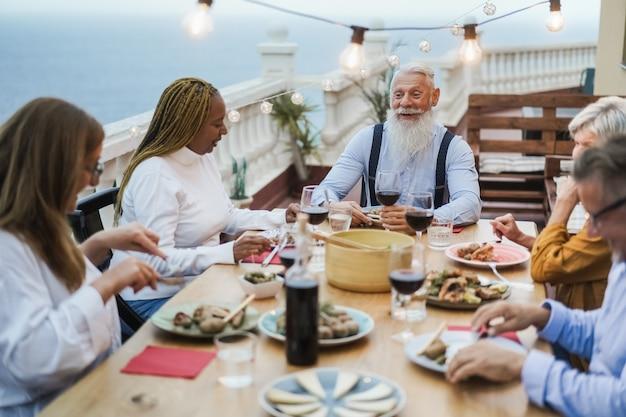 Amis seniors s'amusant au dîner sur le patio - focus sur le visage masculin hipster