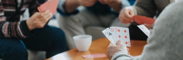 Des amis seniors s'assoient à une table basse et jouent aux cartes