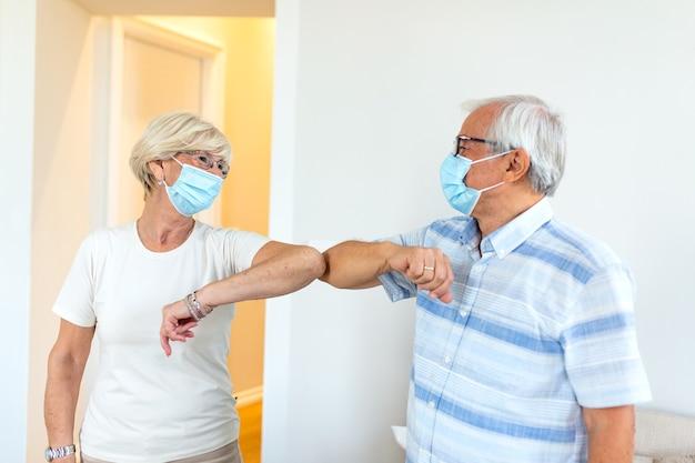 Amis seniors souriants amicaux gardant la distance sociale