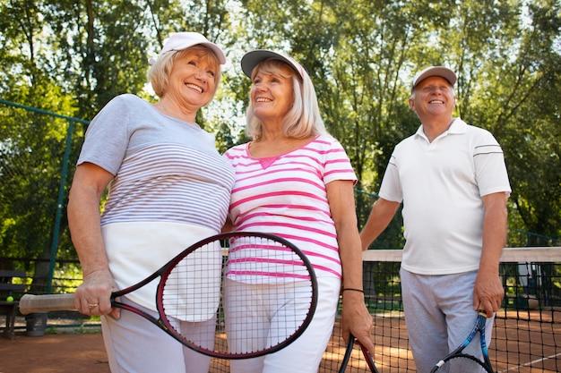 Amis seniors souriants de coup moyen avec raquette