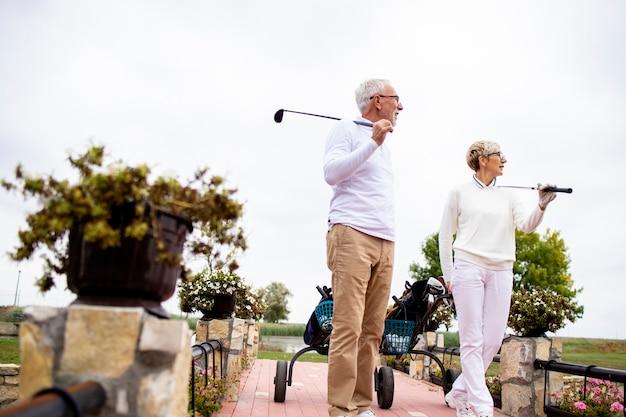 Amis seniors transportant du matériel de golf sur le parcours pour jouer au golf ensemble.