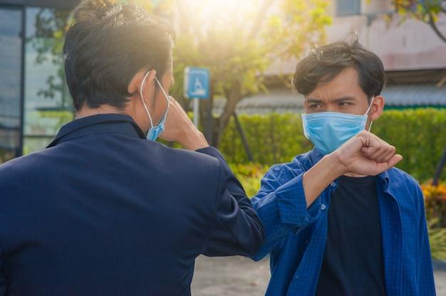 Des amis serrent le coude de la main, nouvelle norme pour prévenir le coronavirus covid19