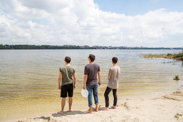 Amis de sexe masculin debout regardant la rivière