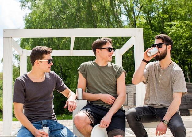 Amis de sexe masculin se détendre avec des boissons rafraîchissantes