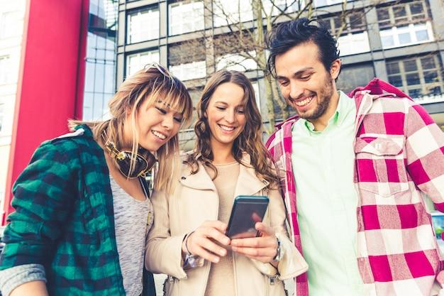 Amis avec smartphone dans la ville