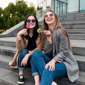 Amis smiley assis dans les escaliers