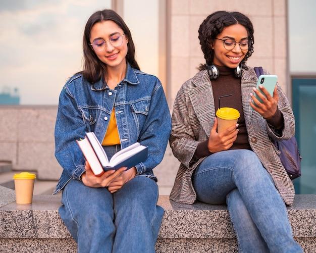Amis smiley avec des livres prenant un café ensemble à l'extérieur