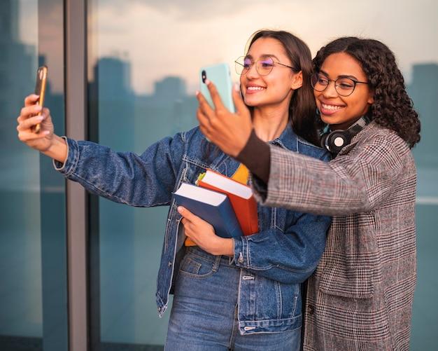 Amis smiley avec des livres prenant des selfies ensemble