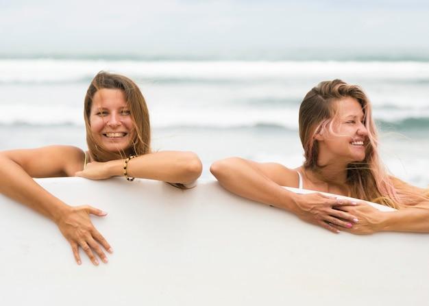 Amis de smiley à la plage avec planche de surf