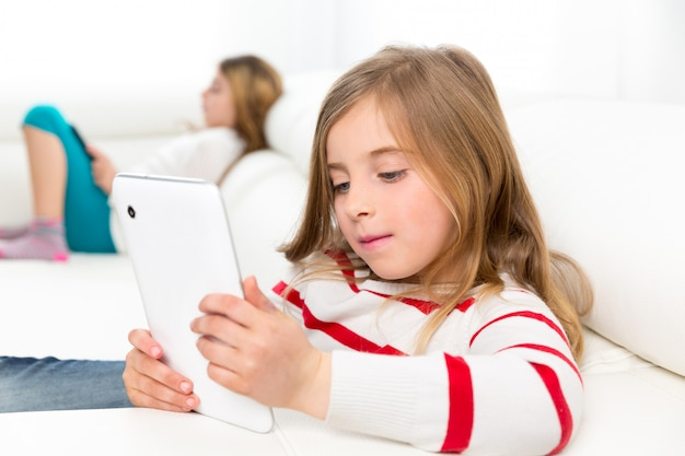 Amis soeur kid filles jouant avec tablet pc dans le canapé