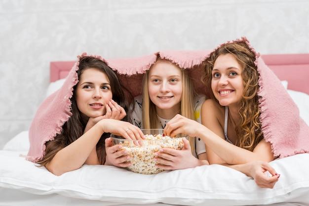 Amis en soirée pijama mangeant du pop corn