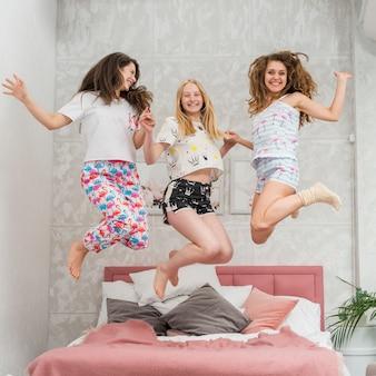 Amis en soirée pijama sautant sur le lit