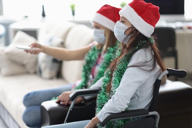 Des amis sont assis en fauteuil roulant et regardent la télévision.