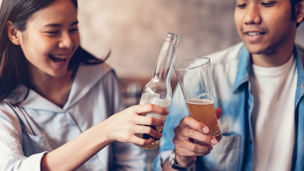 Des amis sont souriants, font la fête au bar, discutent et clochent des bouteilles avec bever