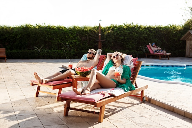 Amis souriant, buvant des cocktails, allongé sur des chaises près de la piscine