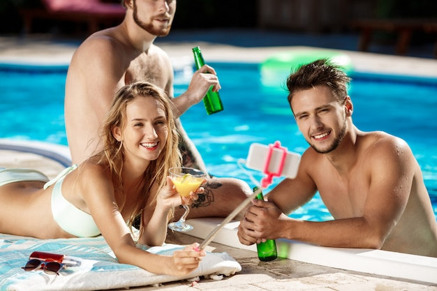 Amis souriant, faisant selfie, buvant des cocktails, relaxant près de la piscine