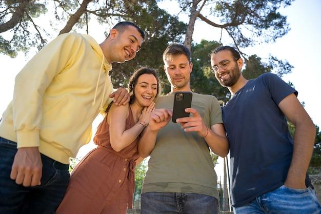 Amis souriant, ils regardent le même téléphone portable