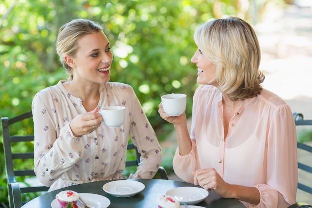 Amis souriants appréciant le café ensemble