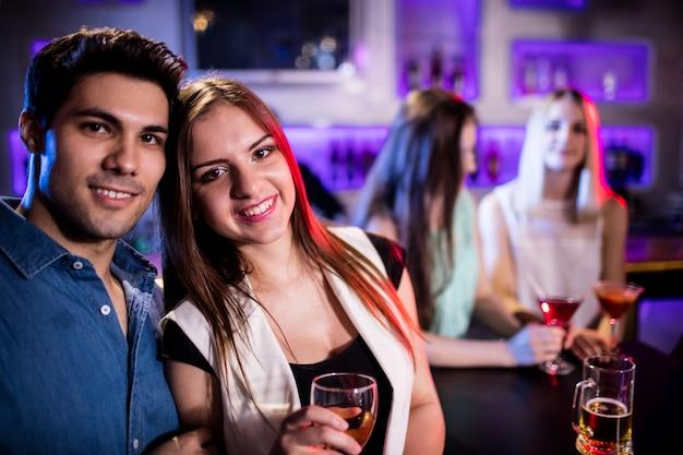 Amis souriants ayant un verre de vin au bar