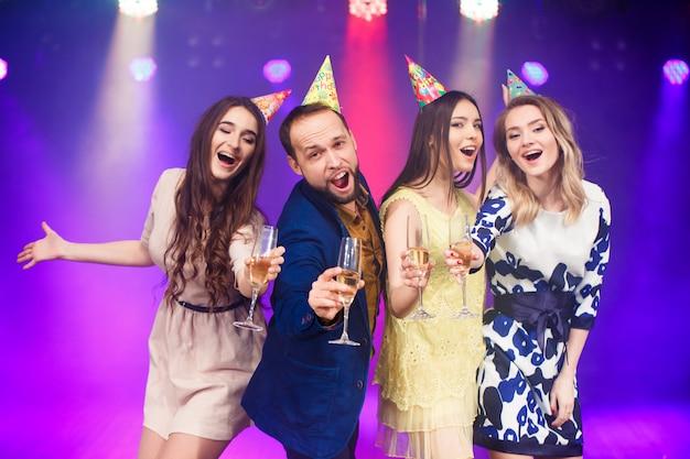 Amis souriants avec coupes de champagne en club
